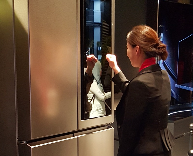 A staff member demonstrating how the opaque compartment of the refrigerator becomes transparent with a knock.
