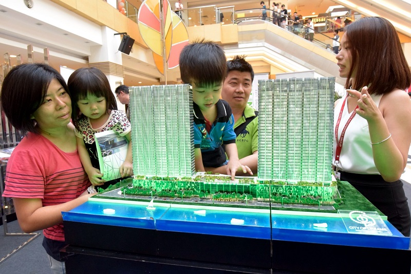 Rapt attention: Zeon Properties marketing executive Iris Wooi (right) talking to Cheah Chee Phon and wife Teoh Hui Chiu as their son Zheng Xuan takes a much closer look at the display model, at the StarProperty.my Fair 2016 in Sunway Carnival Mall, Seberang Jaya.