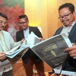 Attendees browsing the ILAM special pullout by StarProperty.my at the ILAM Gala Night Dinner.