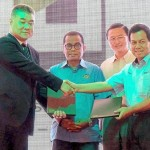 Ismail (right) exchanging documents with Wu (left) to establish the Iskandar Malaysia Greenland Smart City Experimental Centre. Looking on is Mohamed Khaled (second from left).