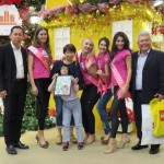 One of the children from PKKI, Len Jye Erl (in the middle) showing her artwork during the gift presentation ceremony with Mr. HC Chan, Mr. Kevin Tan and delegates of Miss Tourism International.