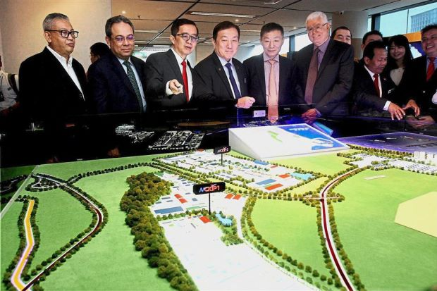 Good project: (from left) Sime Darby Property Bhd CEO Datuk Wan Hashimi Albakri, Malaysian Investment Authority CEO Datuk Azman Mahmud, Malaysia-China Kuantan Industrial Park (MCKIP) chairperson Datuk Soam Heng Choon, Minister of International Trade and Industry II Datuk Seri Ong Ka Chuan, Guangxi Beibu Gulf International Port Group chairperson Zhou Xiaoxi and the East Coast Economic Region Development Council CEO Datuk Seri Jebasingam Isaace John checking out the layout plan of MCKIP at the opening of its office at Wisma Selangor Dredging, Kuala Lumpur.