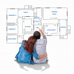 Young attractive couple in love happy together planning and pointing  blueprints , floor plan and design of new house, home, flat or apartment  imaging the distribution of the rooms in real state concept