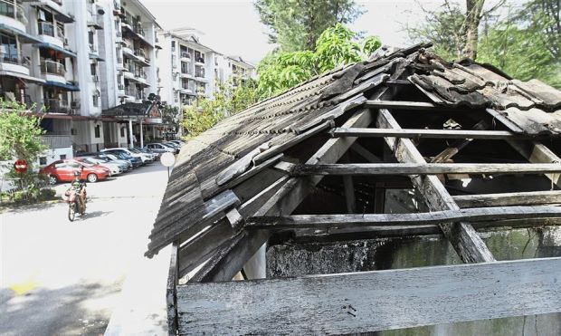 The roof over the garbage bin in the condominium compound left in disrepair.