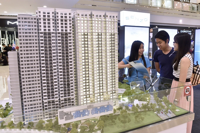 (From left) Sales executive Ang Wei Ting briefing Niam Ham Kiang, 29, and Ong, 27, on the Senzo Residence project at the Corfield Development Sdn Bhd booth. -Pix by GARY CHEN