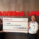 Rose Lai (left) receiving a mock cheque on behalf of grand-prize winner Ho from Gamuda Land marketing and sales general manager Simon Phang at Bukit Bantayan Residences, Kota Kinabalu