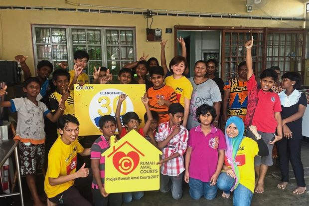 Courts Malaysia marketing director Low Bee Yin (second row, in yellow T-shirt) and staff volunteers with children from Pusat Jagaan Kanak-Kanak Istimewa Lagenda, Klang. (Right) Courts Malaysia staff volunteers giving the interior of Rumah Kasih Sayang in Rawang a fresh coat of paint.