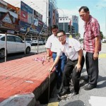 Liew showing the 0.9m-wide and 0.6m-deep pothole at the traffic light junction in Jalan Cheras Indah.