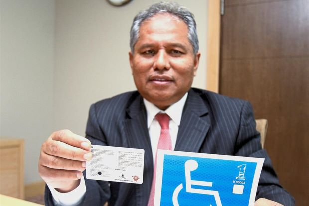 Nadzri holding the A and A1 category for motorcycle and car licence for the disabled respectively. He is also holding the JPJ-approved car sticker for the disabled.