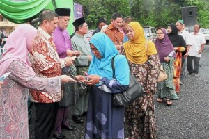 Azmin (second from left) presenting monetary aid to villagers in Hulu Langat who were affected by the floods on June 17.