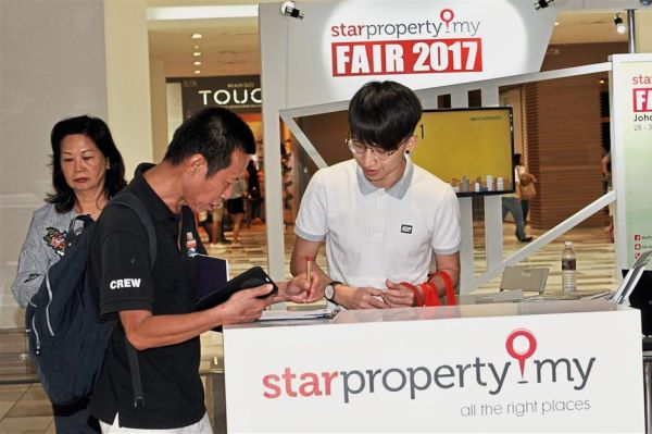A visitor filling up a survey form during the StarProperty.my Fair in Johor Baru.
