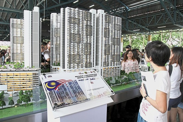 Visitors checking out a scale model of Residensi Desa Satumas.