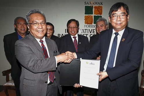 Wong (right) and Unimas vice-chancellor Prof Datuk Dr Mohamad Kadim Suaidi exchanging documents after the MoU signing in Kuching.