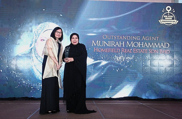 Lim (left) presenting the Outstanding Agent Award to Homefield Real Estate Sdn Bhd director Munirah Mohammad.
