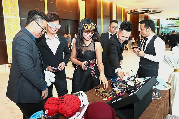 IQI Realty Sdn Bhd team members choosing props at the photo booth.