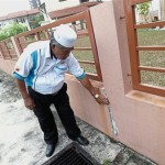 Husin Idris pointing out the cracks on the walls at his home in Bandar Kinrara.