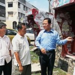 Leong (right) looking at the missing public pay phones with the residents.