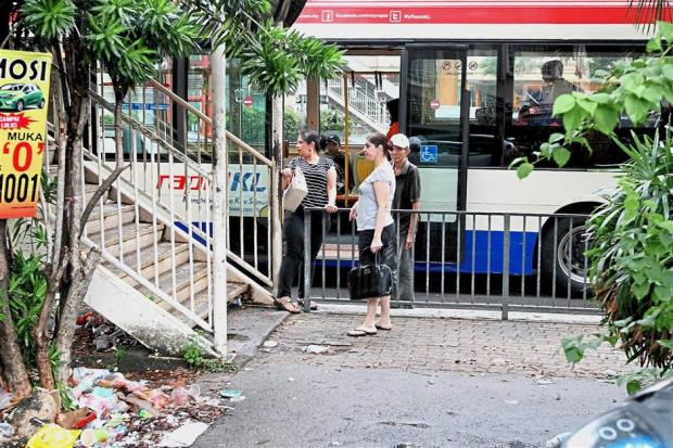 Passengers alighting from a bus that stopped near a pedestrian bridge instead of a bus stop that is 400m away, in Subang Jaya. Read more at http://www.thestar.com.my/metro/metro-news/2017/10/12/riddled-with-obstacles-broken-pavements-and-dangerous-road-crossings-among-problems-faced-by-pedestr/#CL3JG7XDKWZBPpfJ.99