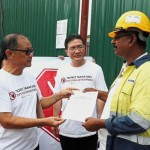 Khong (left) submitting the memorandum to the developers representative (right) as Yeh looks on.