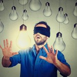 Blindfolded young man walking through lightbulbs searching for bright idea