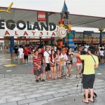 A family taking pictures at Legoland during a visit.