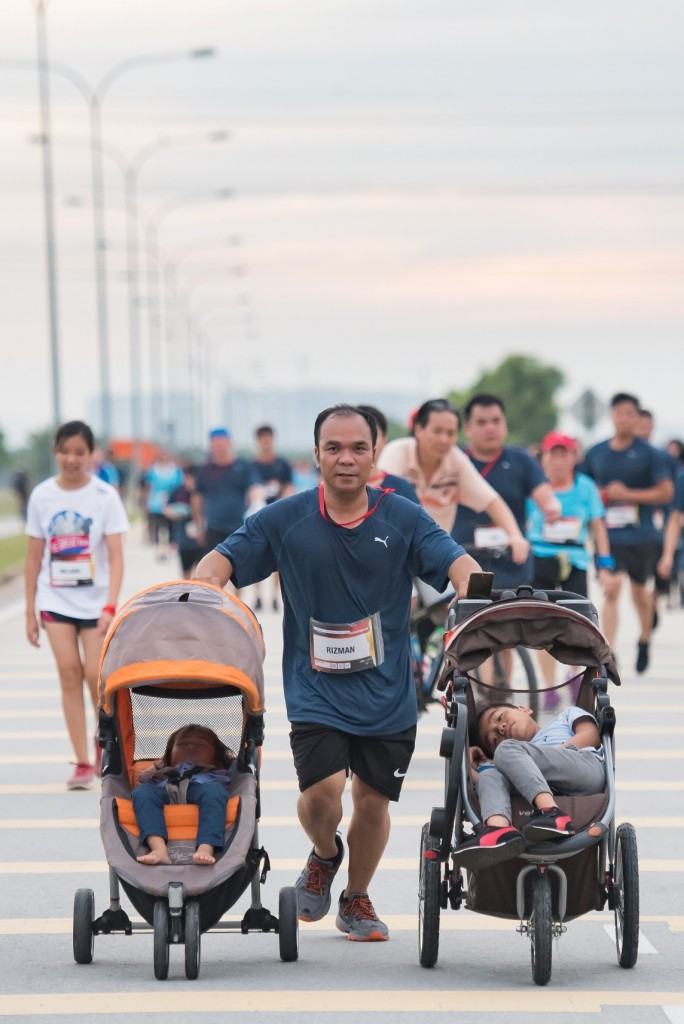 A father of two participating in the run while pushing his children in their strollers. Super dad in action!