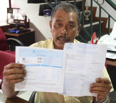 Star filepic. Ibrahim showing his assessment notice and valuation notice he recently received proposing an 300 percent increase in the assessment fee, at his office in Kampung Bharu on Nov 15, 2015.