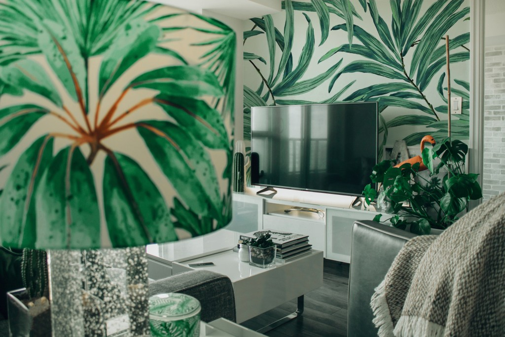 A delightful and striking contrast is created with greenery and representations of leaves juxtaposed against the modern fixtures and upholstery – making for a lush living space that transports residents to a tropical paradise.