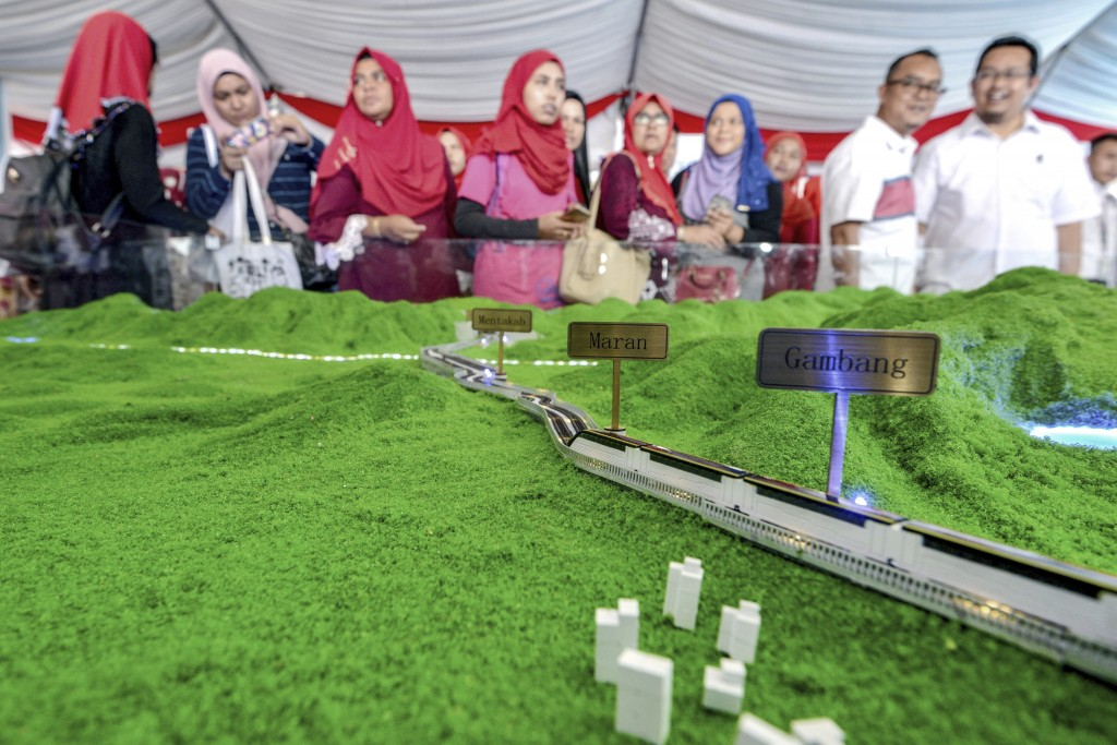 In this Sept. 8, 2017, photo, visitors view a scale model of the ECRL (East Coast Rail Link) during the launching of the train project in Kuantan, east coast of peninsula Malaysia. Malaysia's government says it has decided to resume a China-backed rail link project after the Chinese contractor agreed to cut construction cost by one-third. (AP Photo)