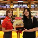 Customer care executive Emily Tyu handing the Sunway Malls Gold Metal Straw to Xera Cheah.