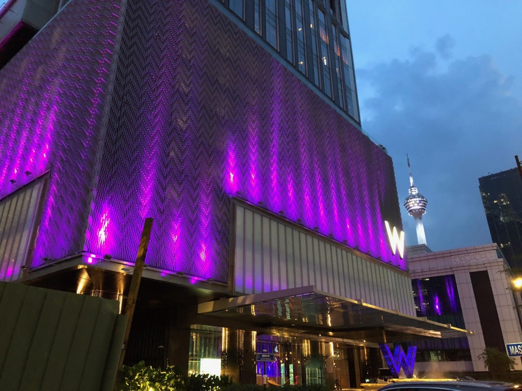At night, the facade of the W Kuala Lumpur lights up in pink and purple.