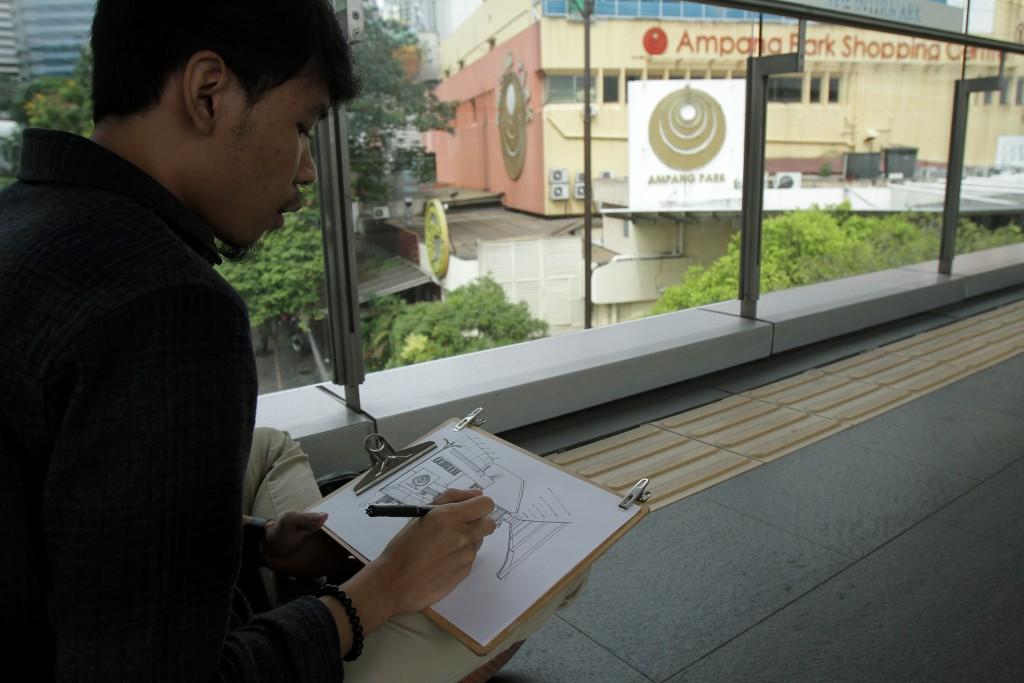 An artist, Zaid Zahuri,  memorialising the façade of Ampang Park from the pedestrian bridge over Jalan Ampang.