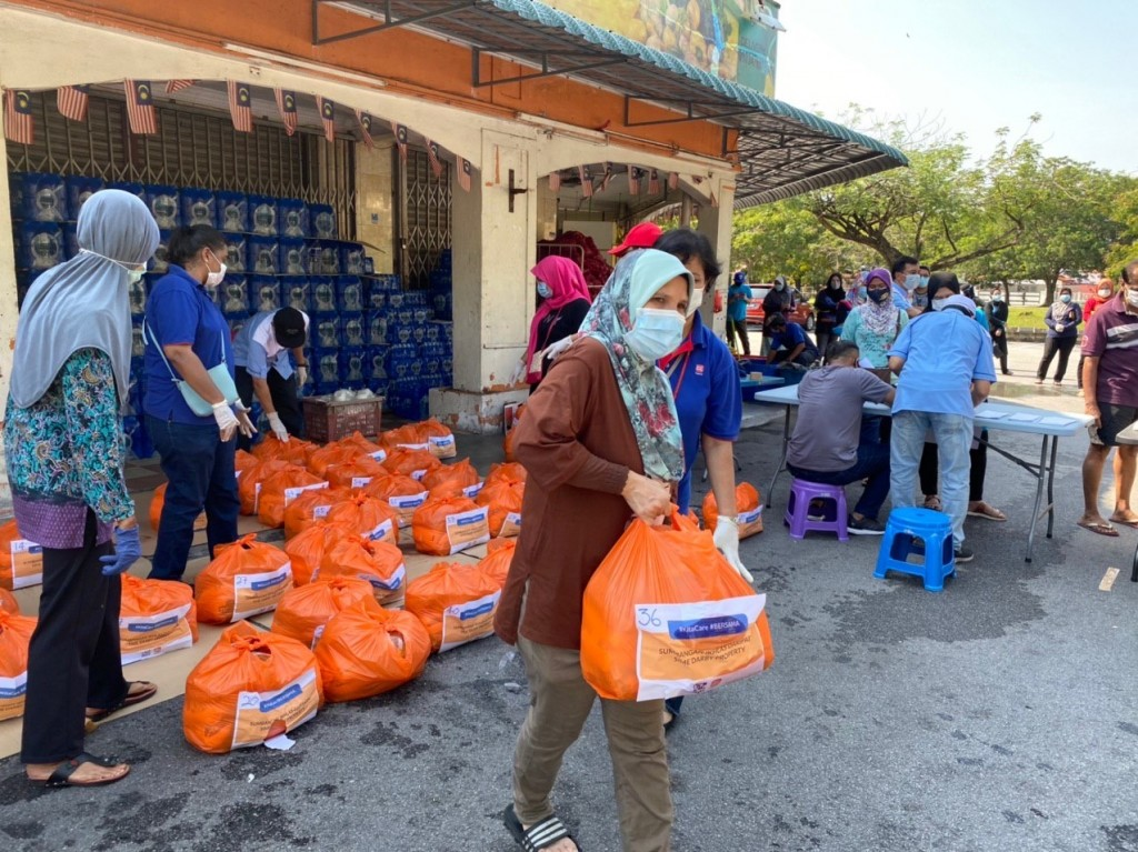 Sime Darby Property business unit employees distributing essential items to nearly 100 families living at the Seri Mutiara Flats in Putra Heights during the MCO.