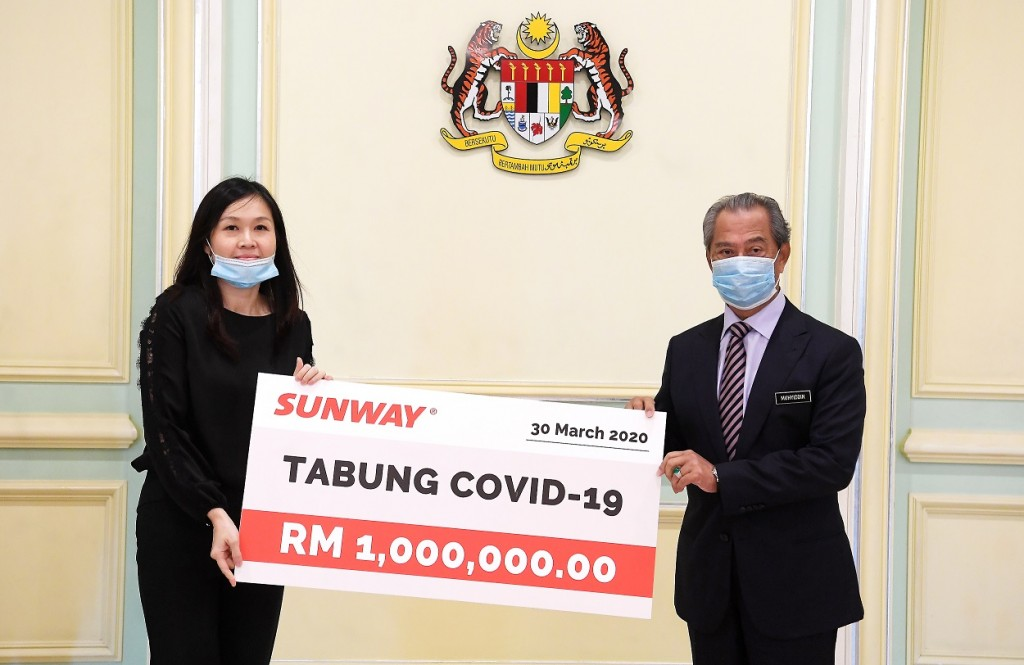 The Prime Minister receiving a RM1mil mock cheque for Covid-19 Fund from Sunway executive director and property division managing director Sarena Cheah.
