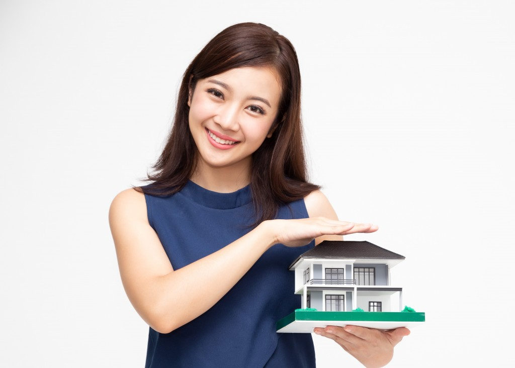 Portrait of beautiful young Asian woman with hands protecting house or home model isolated on white background, Real estate and home insurance concept