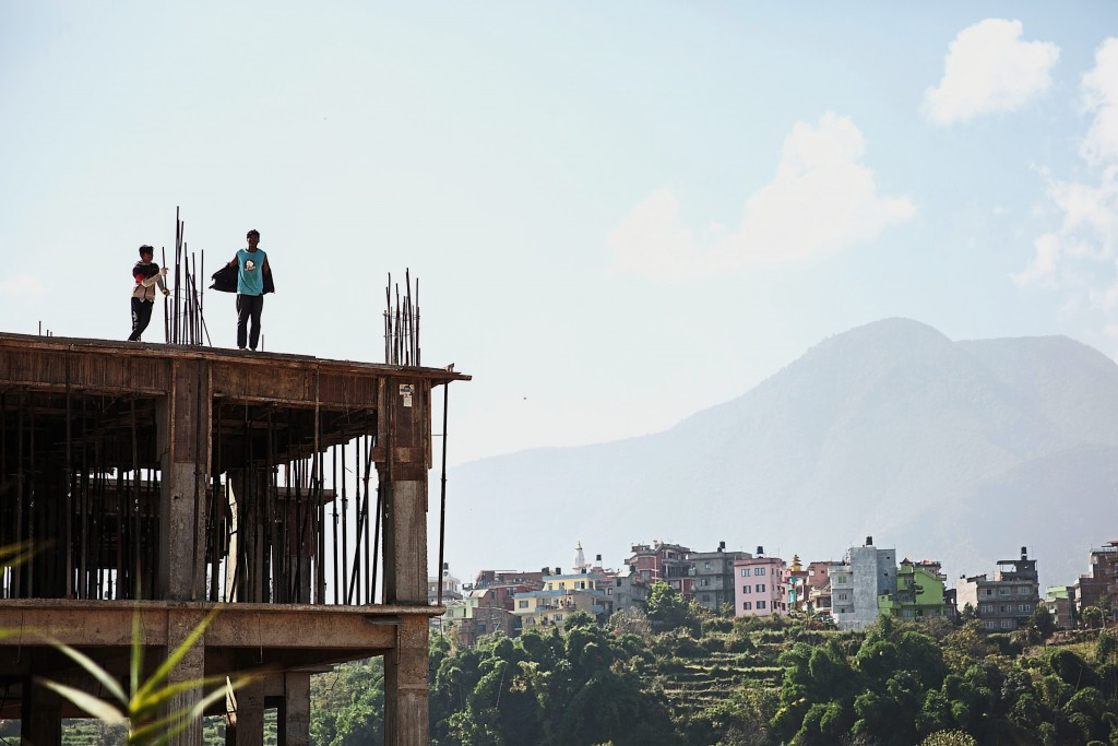 Workers stand on the roof of a commercial building under construction in Kathmandu, Nepal, on Wednesday, Nov. 1, 2017. India and China have often jostled for influence in Nepal, a nation of 28 million people sandwiched between the two Asian giants. While Chinese investment in Nepal has surpassed India, the practical difficulties of transporting people and goods across the world's highest mountains have always pushed Nepal toward India, its largest trading partner. Photographer: Sara Hylton/Bloomberg