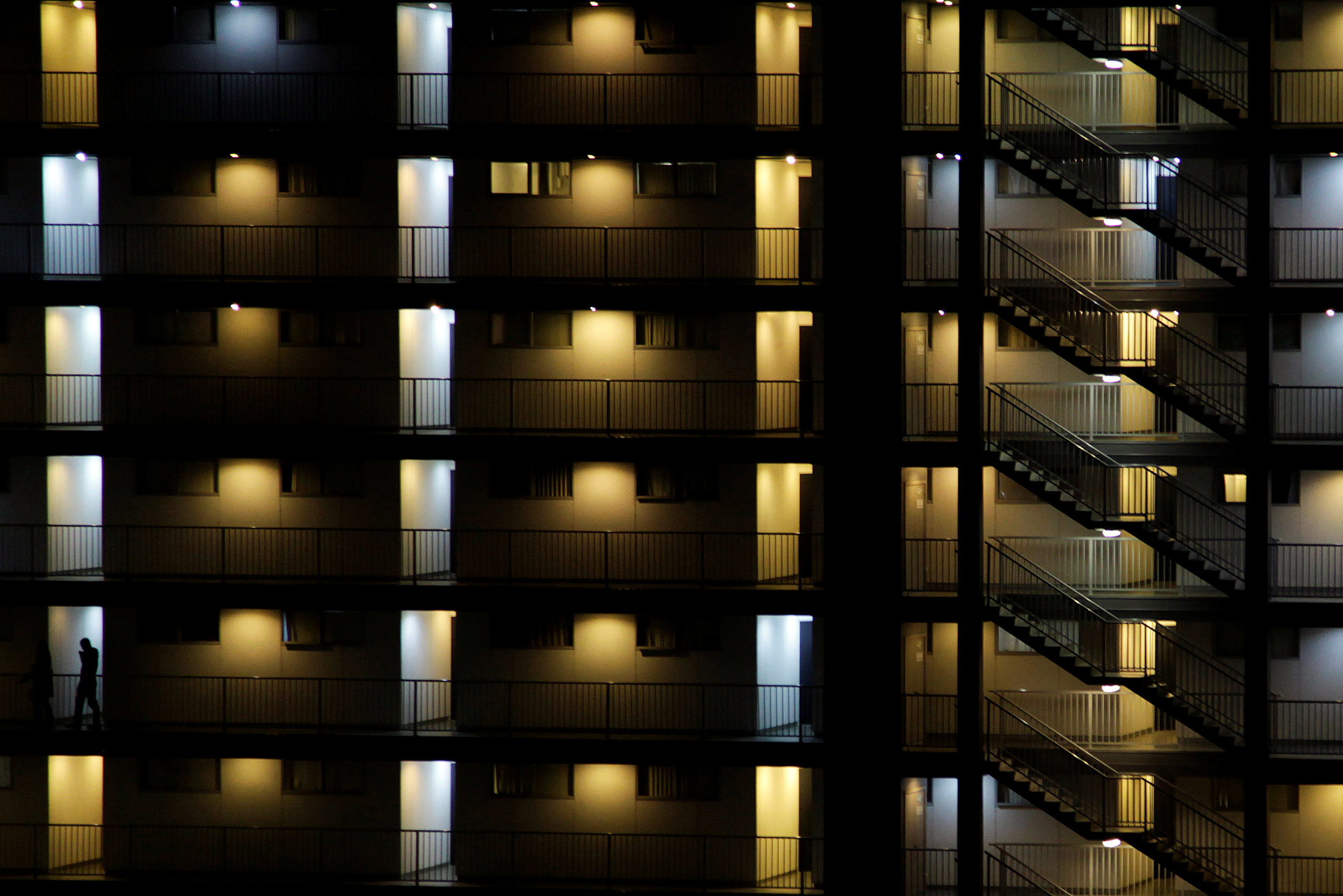 FILE PHOTO: People walk in an apartment building in central Auckland