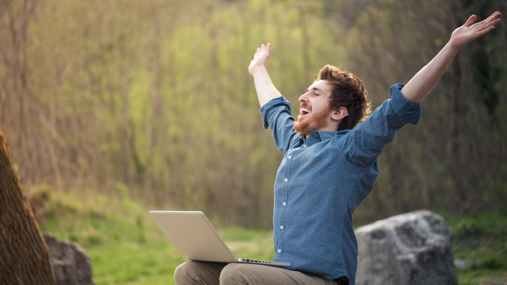 Generic: cheerful hipster man with a laptop sitting outdoors in nature, wifi, wireless, connected