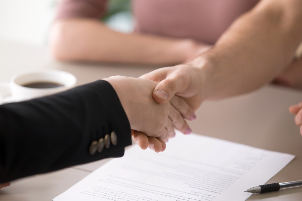 Man and woman handshaking after signing documents, successful de