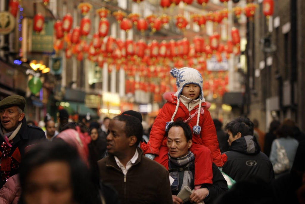 Crowds walk underneath lanterns hanging in Chinatown in London to celebrate the Lunar New Year.