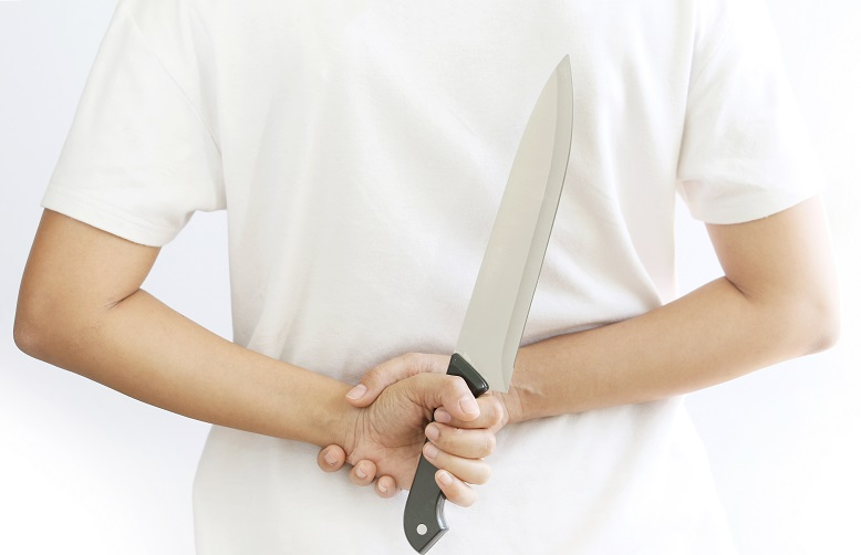 woman hiding kitchen knife.