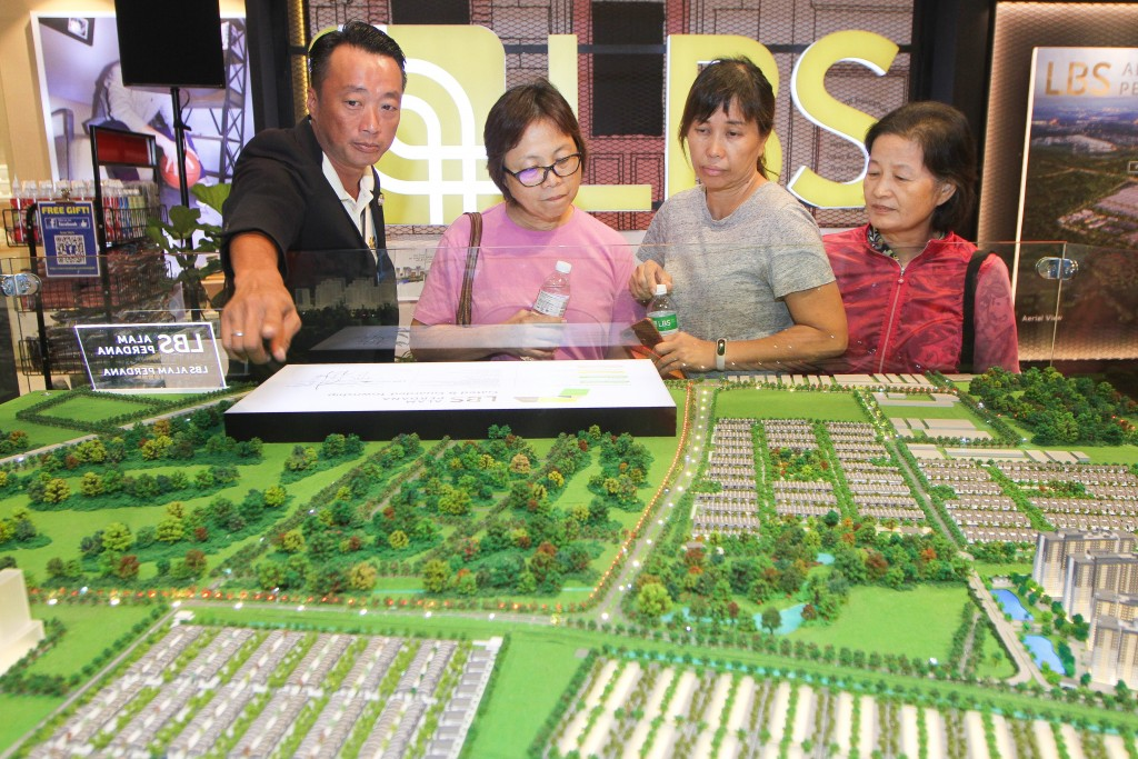 Ore Realty Com Sdn Bhd marketing executive Ken Ng (left) explains the features of the Alam Perdana township to the visitors.
