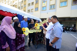 Ahmad Zakiyuddin (second right) and Mohd Salem (right) handing over the mock keys of Selasih Court apartments to villagers of Kampung Mutiara.
