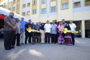 Ahmad Zakiyuddin (seventh right) and Mohd Salem (sixth right) taking a group photo with the villagers of Kampung Mutiara after handing over the mock keys of Selasih Court to them