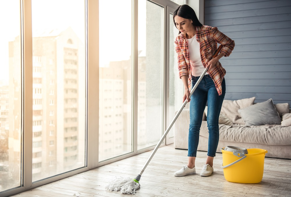 Beautiful young woman is smiling while cleaning floor.