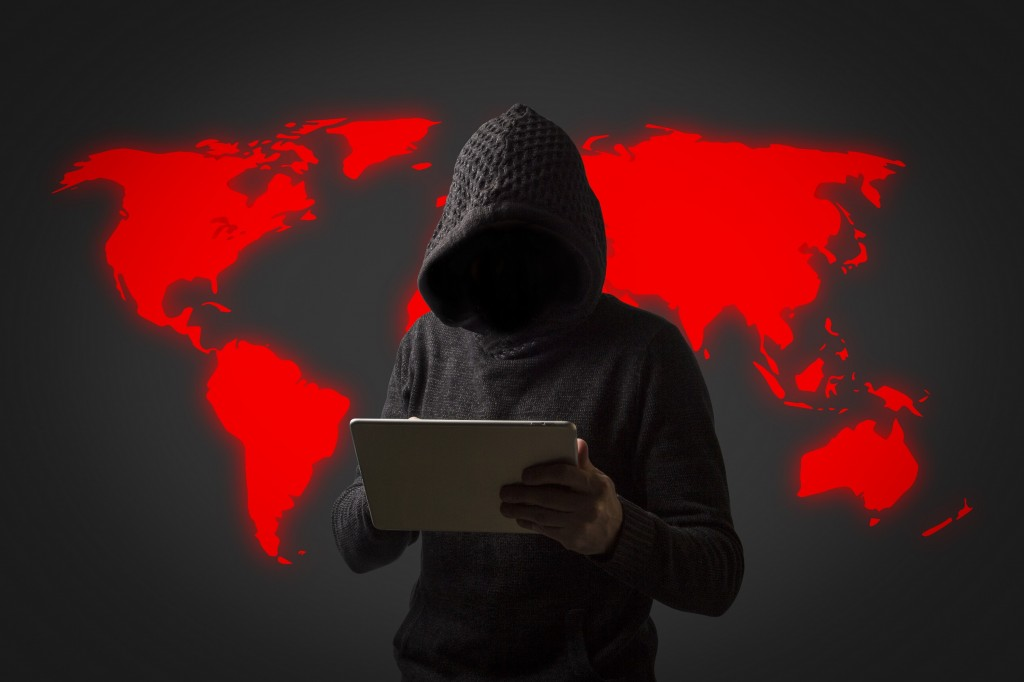 Faceless man in a hoodie with a hood holds a tablet in his hands on a dark background. Concept of hacking user data. Hacked lock, credit card, cloud, email, passwords, personal files