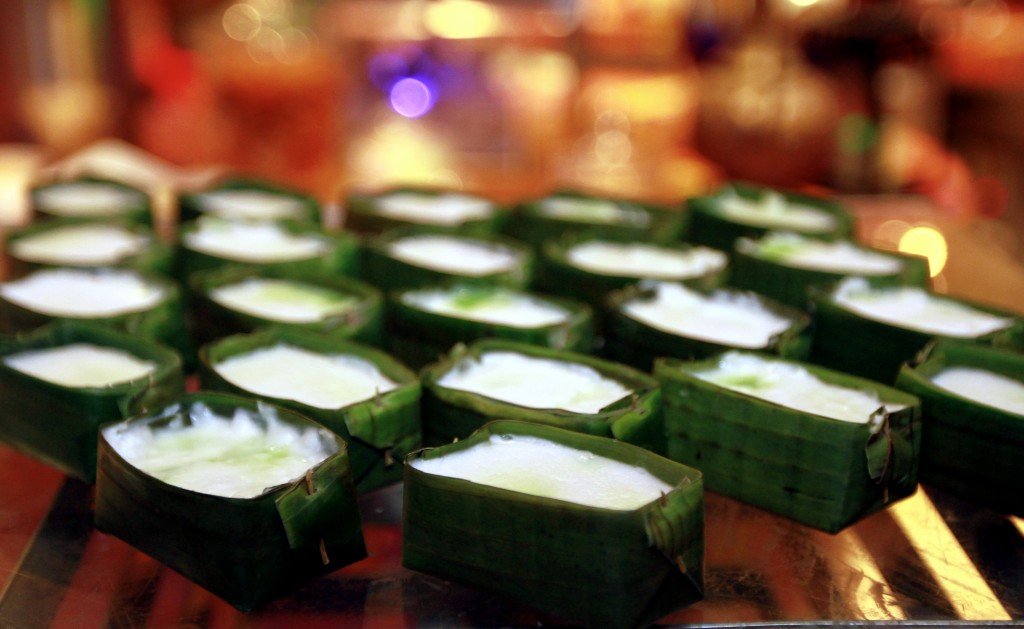 Tepung Pelita combines layers of coconut milk and pandan custard, steamed in little banana leaf or pandan containers.