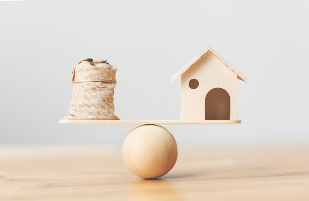 Wooden home and coins money in bag on wood scales. Property investment and house mortgage financial real estate concept