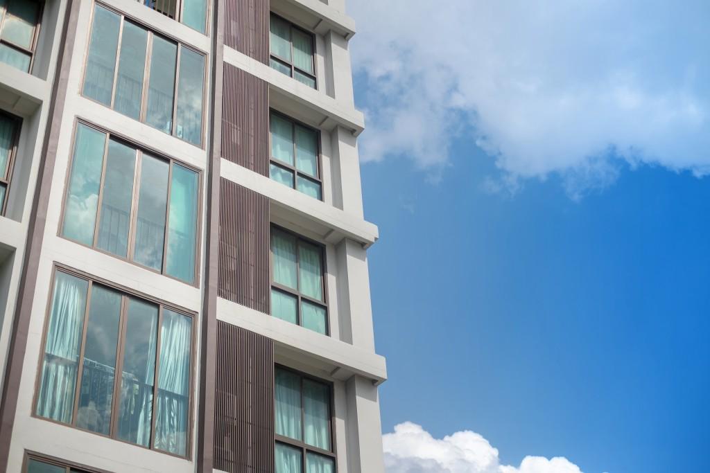 Window grid of modern condominium building with white cloud blue