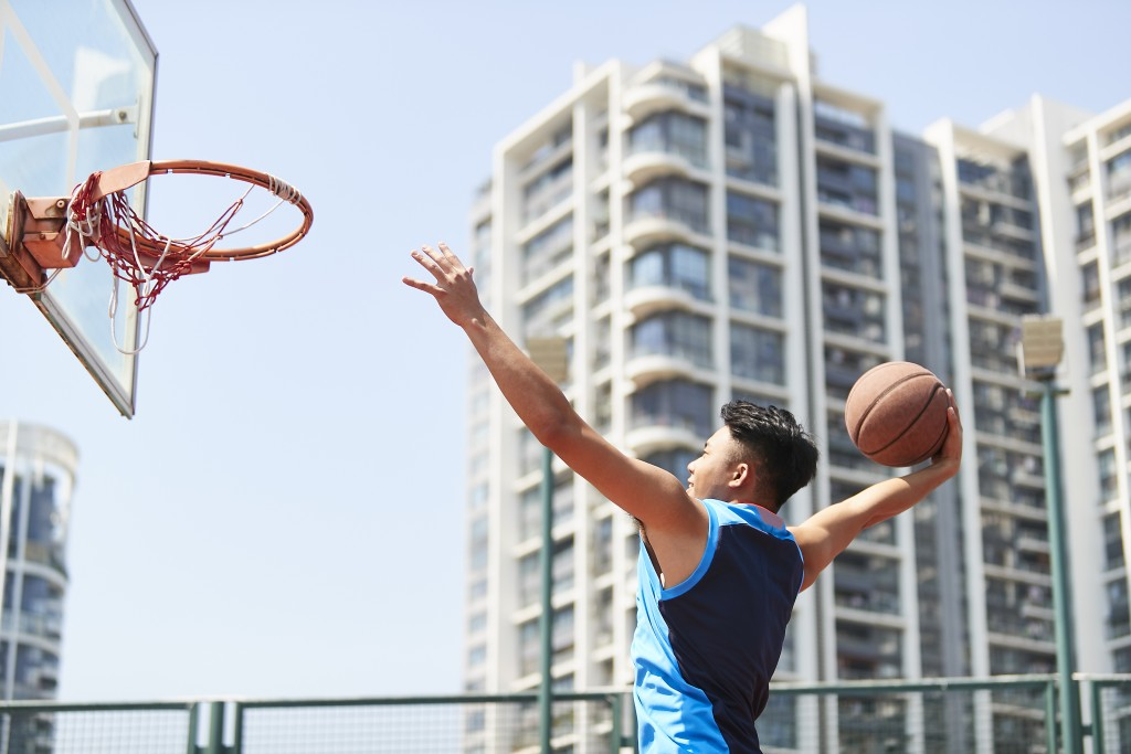 young asian adult dunking